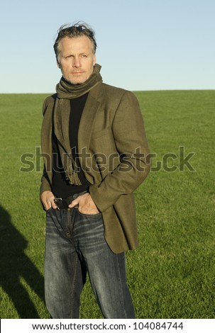 mature man with beard wearing a green scarf and jacket and standing alone in a field. - stock photo