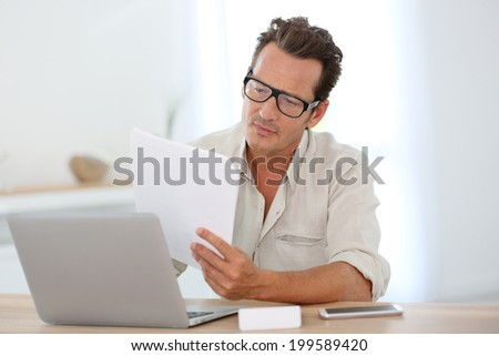 Mature man with eyeglasses working from home on laptop - stock photo