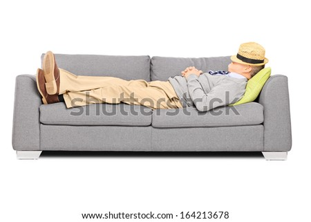 Mature man with hat over his head sleeping on a sofa isolated on white background - stock photo