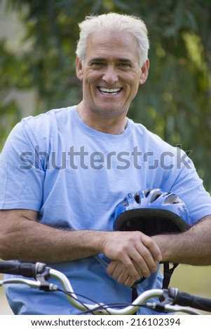 Mature man with helmet on bicycle, smiling, portrait