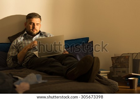 Mature man with laptop on the bed - stock photo