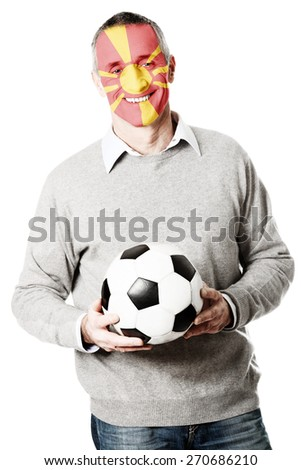 Mature man with Macedonia flag painted on face. - stock photo