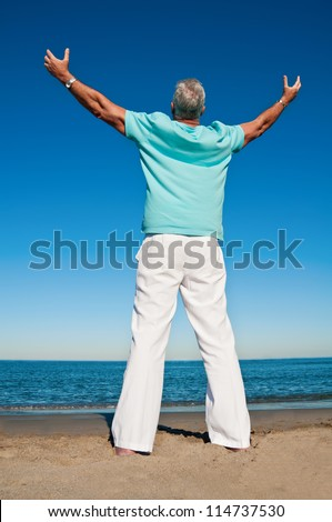 Mature man with open arms at the beach praising the greatness of a higher power