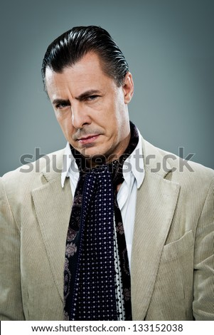 Mature Man with Serious Expression Over a Grey Background - stock photo