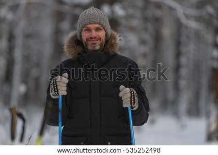 Mature man with ski poles in winter forest