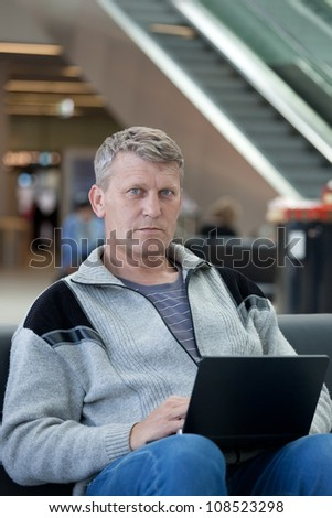 mature man with the laptop in a hall expectation of the international airport