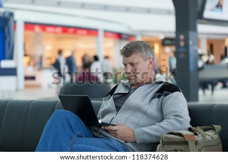 mature man with the laptop in a hall expectation of the international airport - stock photo