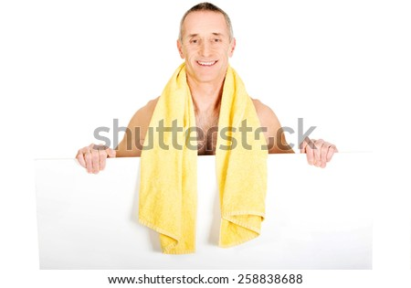 Mature man with towel around neck holding empty banner. - stock photo