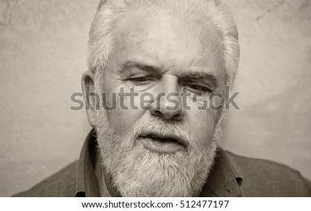 Mature man with white beard talking at home. Family and relax concept.