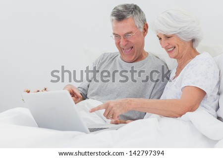 Mature man with wife pointing at a laptop in bed - stock photo