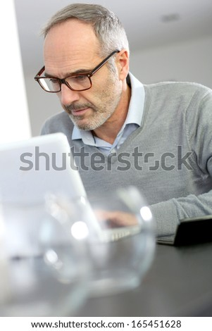 Mature man working from home with laptop computer - stock photo