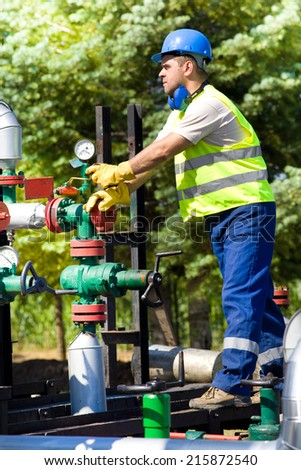 Mature man working on pipes on oil plant  - stock photo