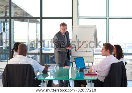 Mature manager reporting to graphs to his team - stock photo