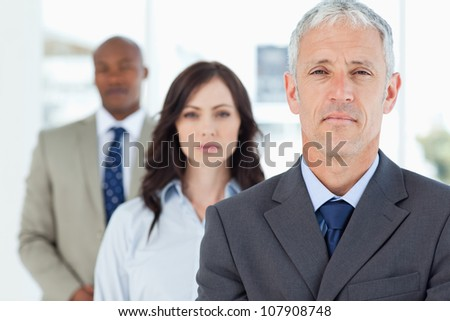 Mature manager standing upright and followed by two serious employees