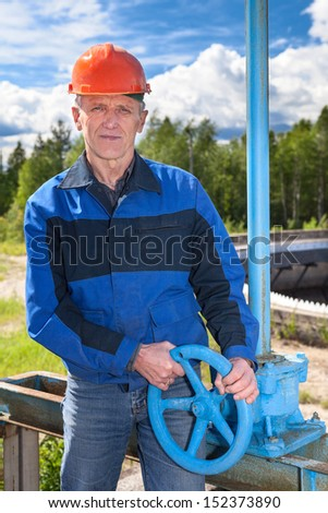 Mature manual worker turning cut-off valve at factory - stock photo