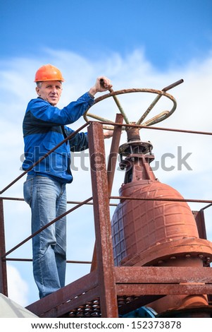Mature manual worker turning huge valve gate at factory - stock photo