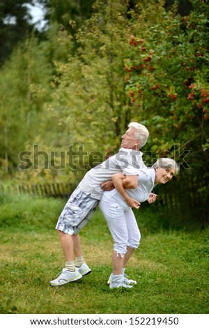 Mature married couple exercising on fresh air in summer