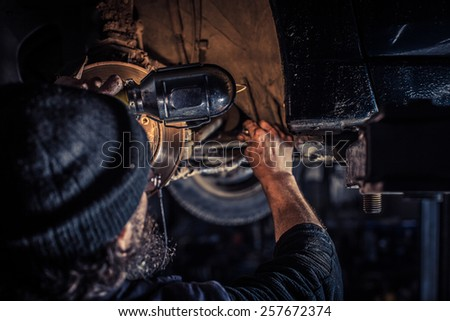 Mature mechanic at repair service station inspecting car suspension - stock photo