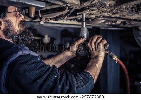 Mature mechanic at repair service station unwound screw - stock photo
