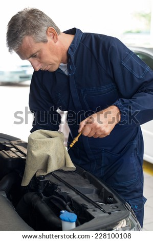 Mature Mechanic Measuring The Oil Level Of A Car Engine In Garage - stock photo