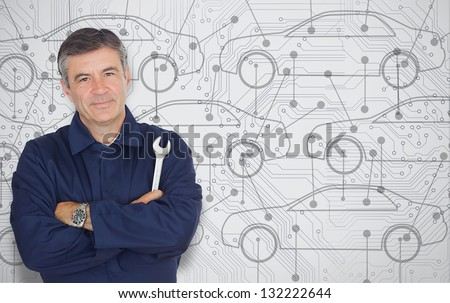 Mature mechanic standing in front of a cars diagram background while looking at camera - stock photo