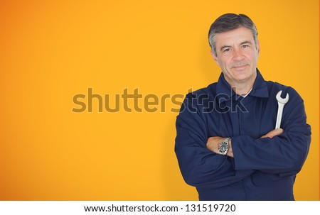Mature mechanic standing in front of yellow background while looking at camera