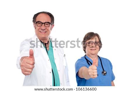 Mature medical professionals showing thumbs up at camera - stock photo