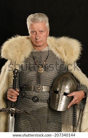 Mature Medieval knight on a dark background - stock photo