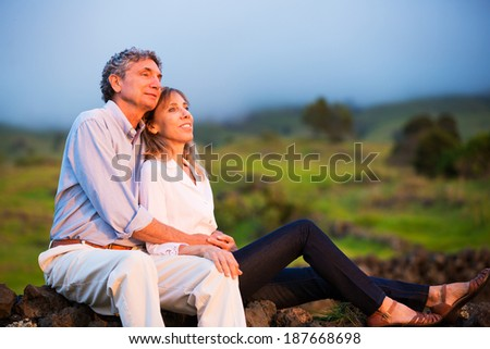 Mature middle age couple in love watching the sunset - stock photo