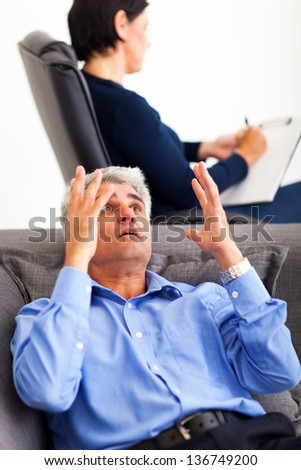 mature middle aged man explaining his problem to psychologist - stock photo