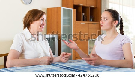 Mature mother and adult daughter having serious conversation in home - stock photo