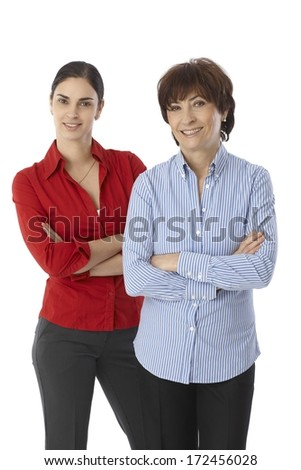 Mature mother and daughter standing arms crossed, smiling. - stock photo