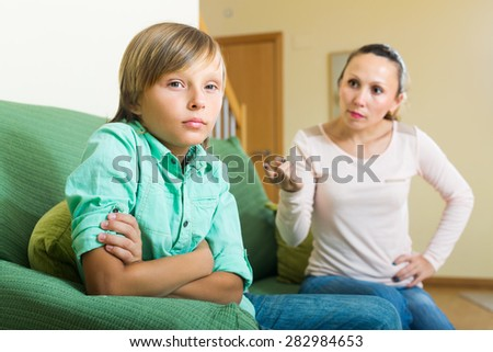 Mature mother and teenager son having conflict in home interior