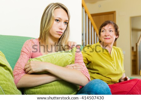 Mature mother asks for forgiveness from adult  daughter after quarrel. Focus on girl - stock photo