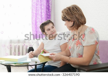 Mature mother helping her child with homework at home. - stock photo