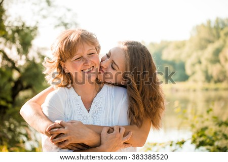 Mature mother hugging with her teen daughter outdoor in nature on sunny day - stock photo