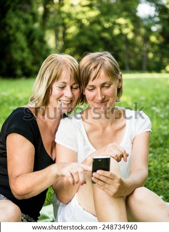 Mature mother showing on mobile phone to her adult child - outdoor in nature - stock photo