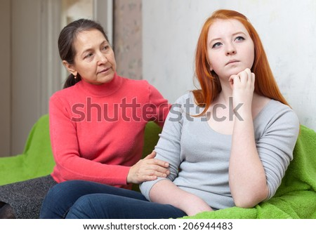 Mature mother tries reconcile with teenage daughter iafter quarrel. Focus on girl