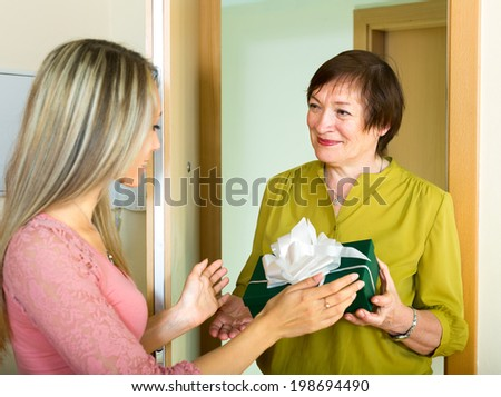 Mature mother visiting adult daughter and giving her a gift - stock photo
