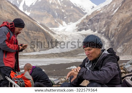 Mature Mountain Guide Looking on Wrist Watch  Group of Climbers Led by Aged Guide Portrait with High Mountains and Glacier Massive Flow on Background - stock photo