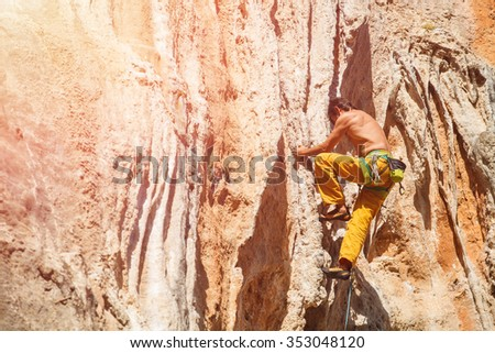 Mature mrock climber on the wall against the blue sky and mountains - stock photo.