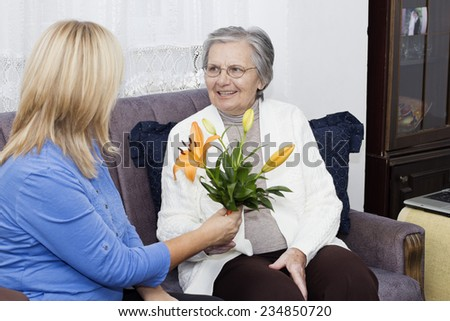 Mature nurse sitting on the sofa and  giving to  senior woman  a bouquet of flowers. - stock photo