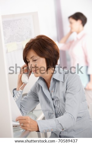 Mature office worker woman using landline phone, smiling, coworker using mobile phone in background.?