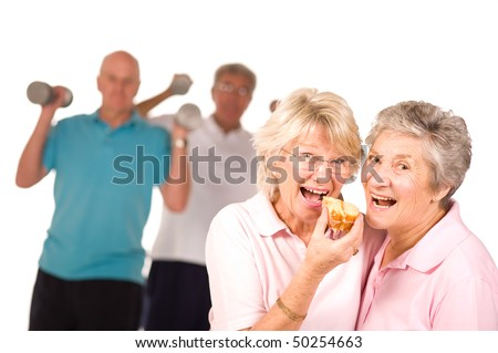 Mature older ladies eating cake with partners working out in the background