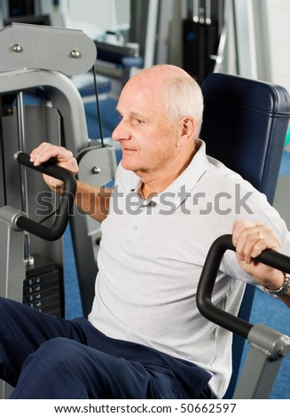 Mature older man working out in the gym - stock photo