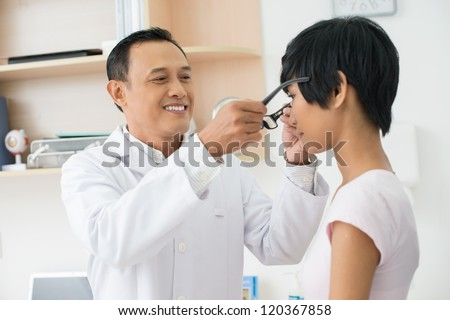 Mature optician giving new eyeglasses to female patient