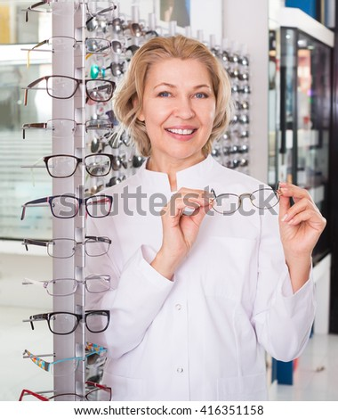 Mature optician posing with glasses in modern optics store