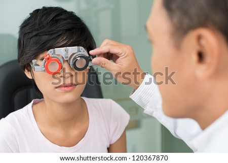Mature optician selecting eyeglasses to female patient - stock photo