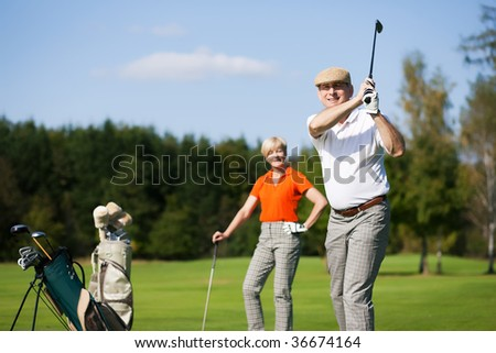 Mature or senior couple playing golf - stock photo