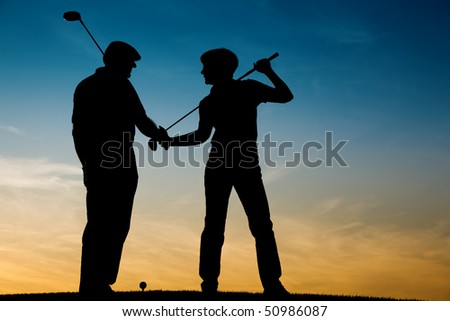 Mature or senior couple playing golf - pictured as a silhouette against an evening sky - stock photo